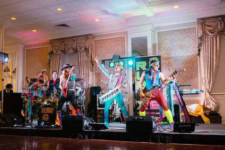"""After dinner, the much-anticipated 1980s cover band Rubix Kube took the stage, kicking the party into high gear. """"We wanted something different from the typical wedding band, so we both jumped on the idea of an '80s cover band,"""" Natalie says. """"They really got everyone on the dance floor with their fun lighting and wild '80s costumes."""" Props like crazy wigs, glow sticks, sunglasses, sweatbands and more went a long way with guests and got everyone into the throwback spirit."""
