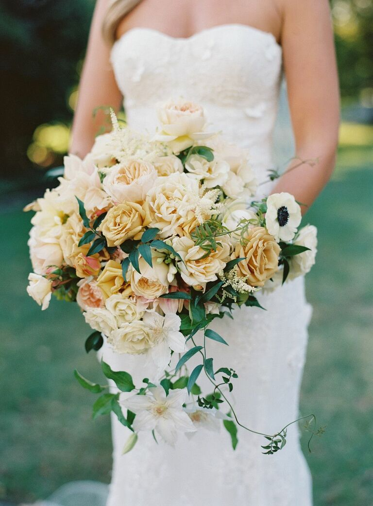 Bride holding yellow-and-white bouquet