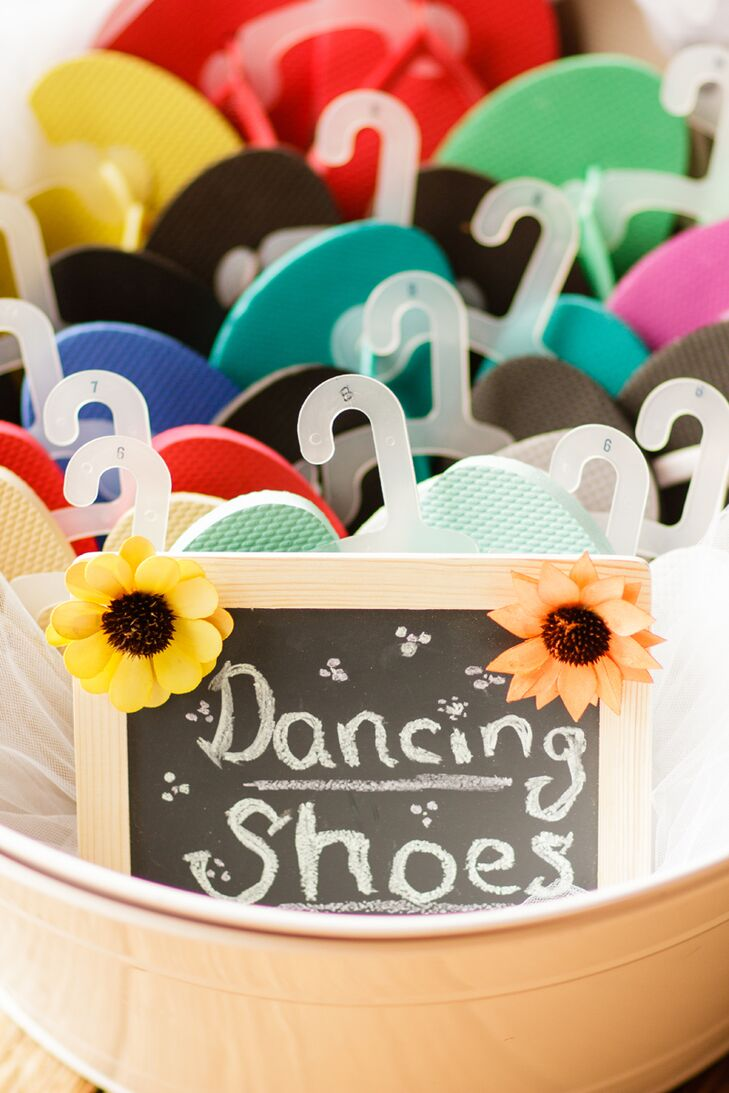 """The couple got creative and made sure every guest was ready to hit the dance floor to the North Mountain Ramblers folk band. Multiple sizes of bright flip-flops were waiting in a tub with a """"dancing shoes"""" chalkboard sign, so guests knew the gift was for them."""