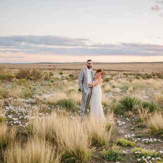 Couple standing in a field in Texas at sunset