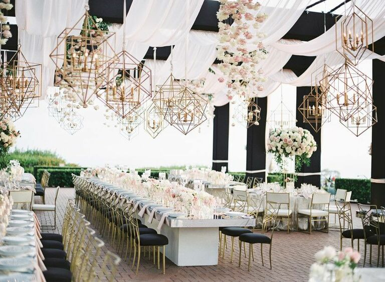 Al fresco wedding reception with gold chandeliers and glam black-and-white details
