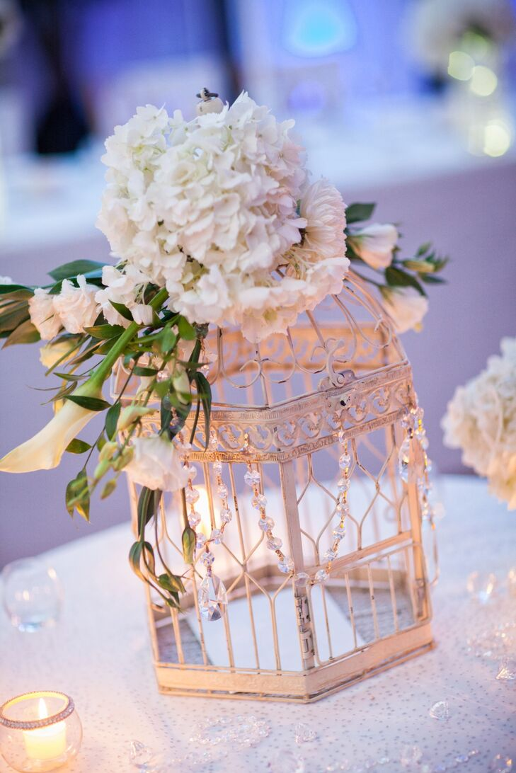 Guests placed their cards in a vintage birdcage topped with a bunch of white flowers.