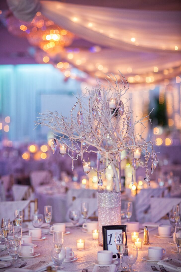 The reception tables were topped with arrangements of white-painted branches dripping with strands of crystals.