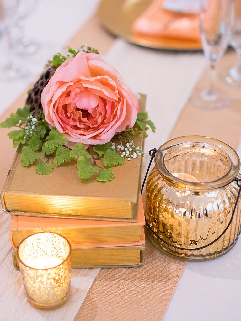 Silk wedding reception flowers styled with book stacks