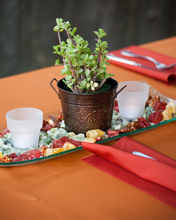 The centerpieces were on long glass plates covered with green sea glass, red and gold rocks and succulents in copper pots framed by two LED candles.