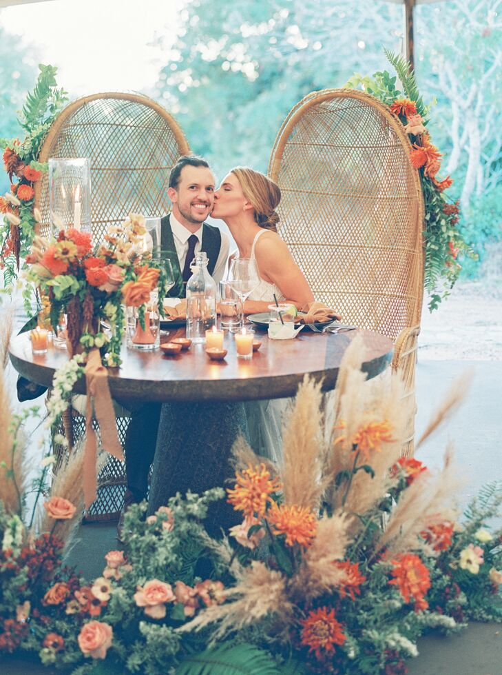 Couple in Rattan Sweetheart Table Chairs at The Greenhouse at Driftwood