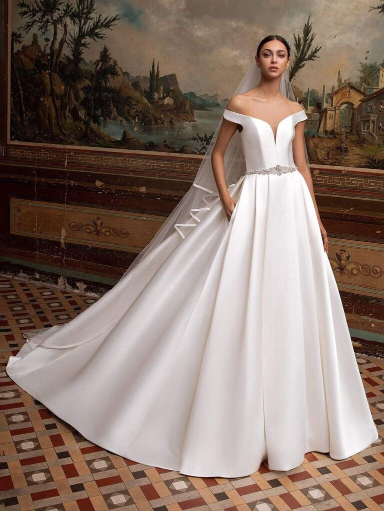 Cửa hàng cô dâu camellia váy cưới trễ vai màu trắng trơn với đường viền cổ yếm với túi thắt lưng đính hạt v sâu và váy dạ hội xếp li váy cưới màu trắng đẹp