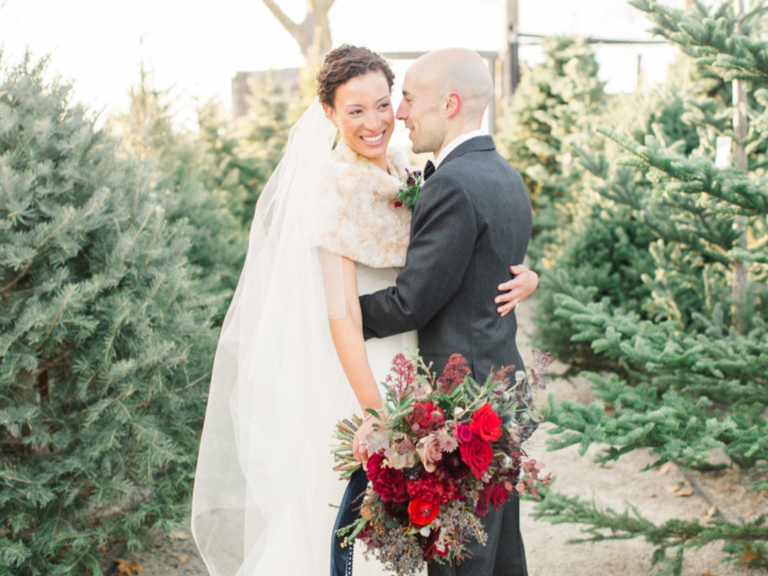 Couple sharing hug surrounded by Christmas trees