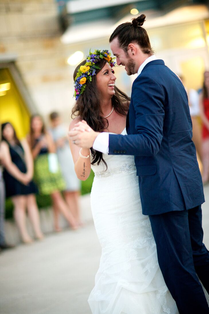 Chelcie wore a trumpet-style lace and taffeta wedding dress for her garden wedding. She completed her look with pearls from her family and a bold yellow and purple flower crown that went with the purple, yellow and green palette.