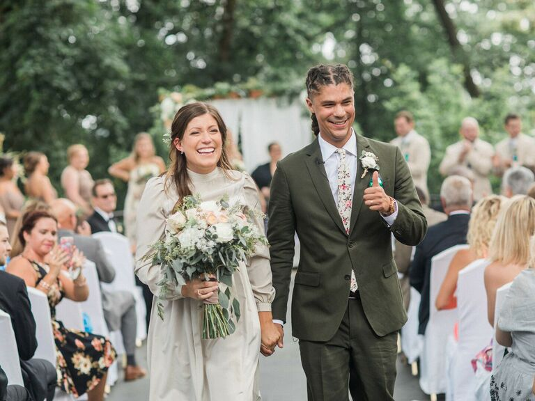 Couple smiling and laughing down aisle