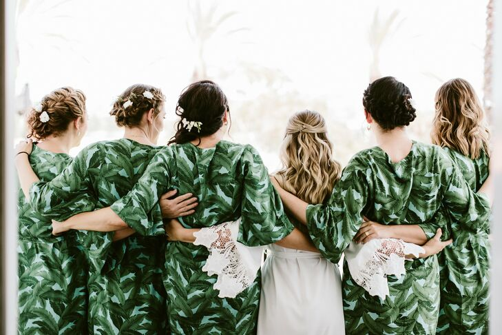 Mira's bridesmaids wore their hair in low, loose updos adorned with florals for her wedding to Nate at Leo Carrillo Ranch in Carlsbad, California.