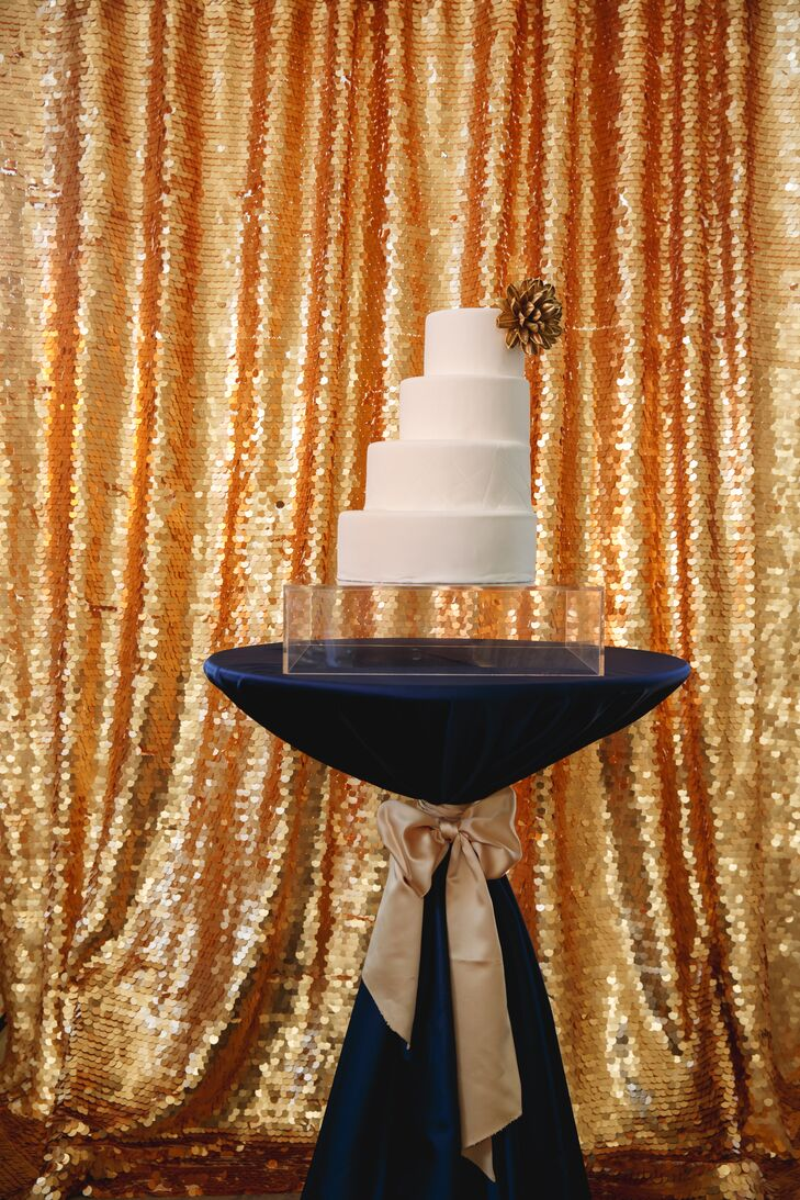 The couple displayed a modern, asymmetrical white cake with a gold floral accent. It appeared suspended mid-air on a transparent cake stand.