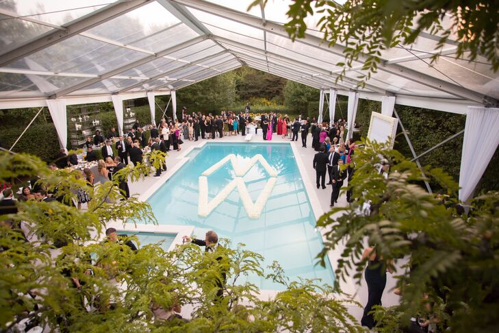 """Fresh white roses were arranged to create a custom """"M"""" and """"W"""" wedding logo that floated in the pool during cocktail hour."""