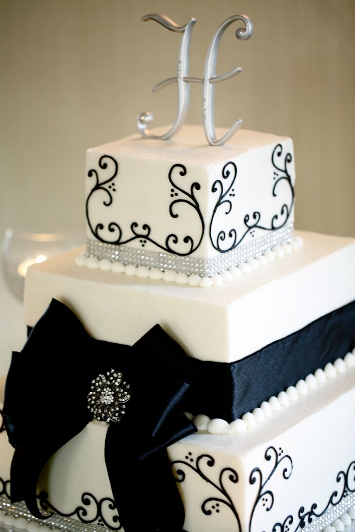 The three-tiered wedding cake was decorated with black design and wrapped with thick black ribbon. The cake topper was the couple's last name initial.