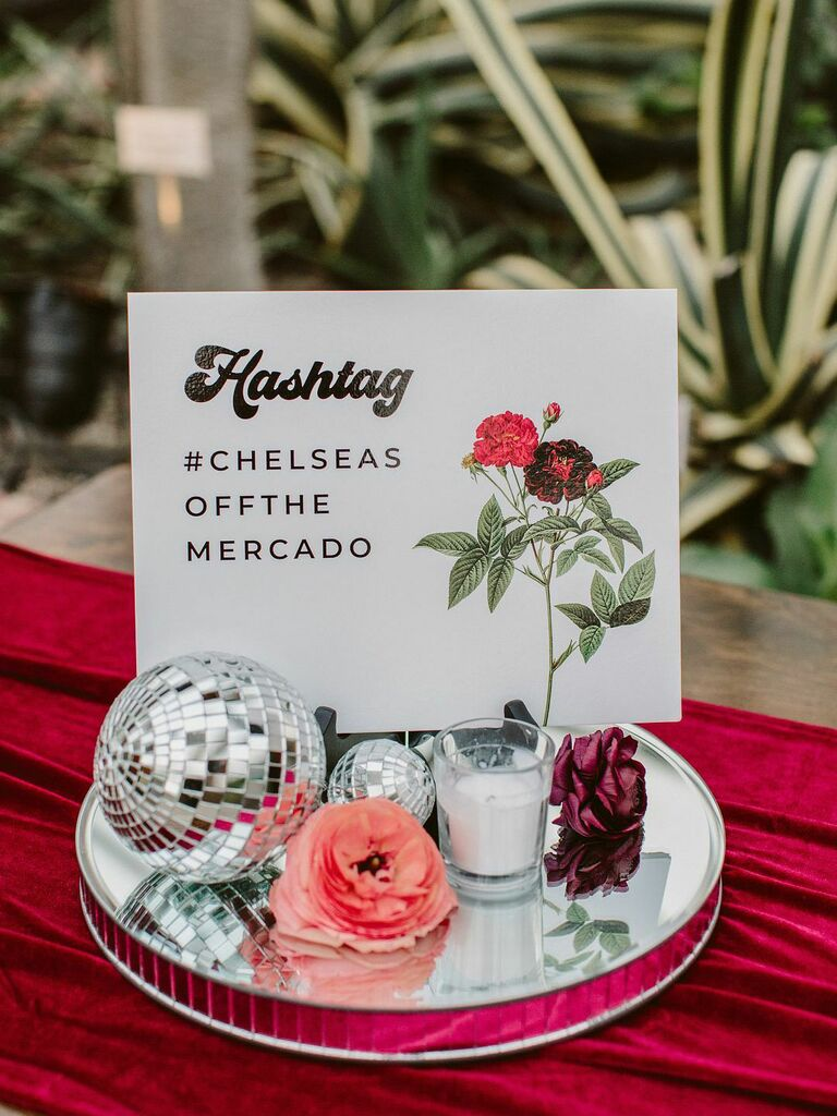 Wedding decor vignette with disco balls, flowers, candles and wedding hashtag sign