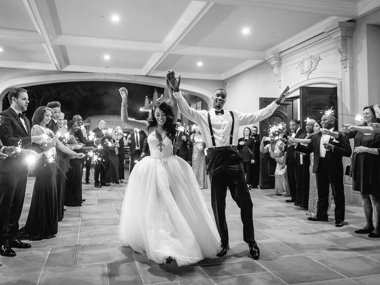 Bride and groom exiting wedding reception surrounded by guests in black-tie optional attire