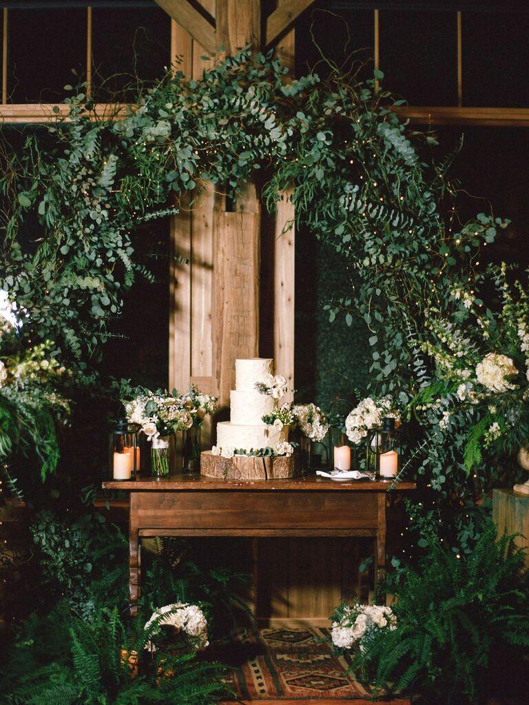 Three-tier rustic wedding cake on tree stump stand under greenery arch