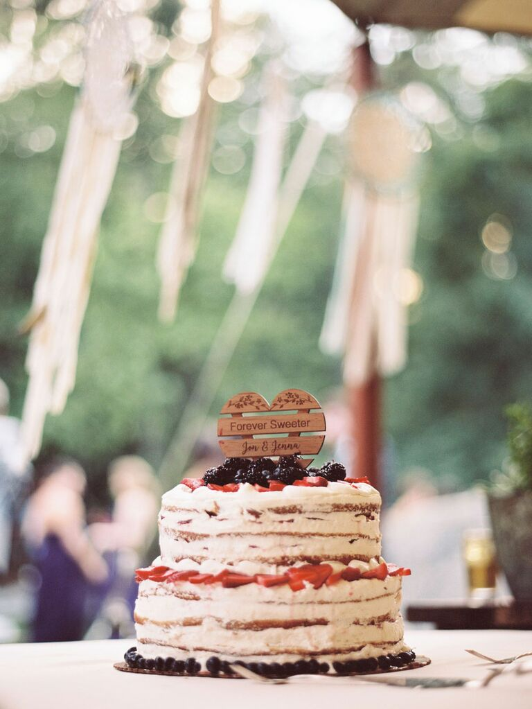 Two-tier rustic wedding cake with fresh berries and custom wood cake topper