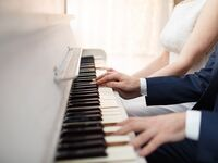 bride and groom play white piano