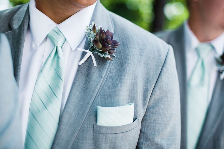 The couple opted for understated elegance when it came to the groomsmen attire. The guys donned matching pale gray suits from Reg Wilkinson's Menswear in Sudbury, Ontario, accessorizing them with striped mint-colored ties and pocket squares, along with purple succulent boutonnieres accented with sprigs of dusty miller.