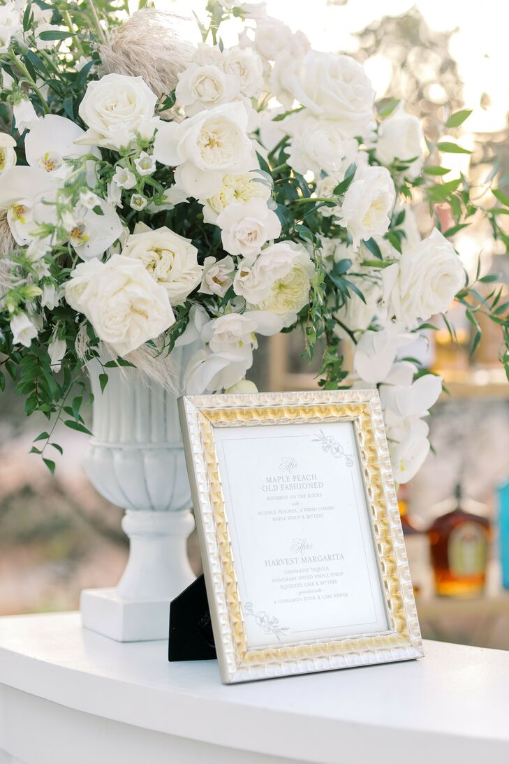 Floral Arrangement With White Orchids and Roses Beside Framed Sign