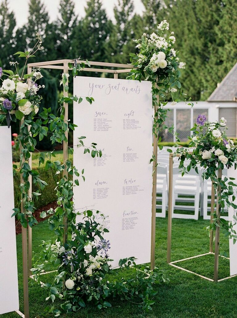 Seating chart suspended from gold structure and covered in greenery