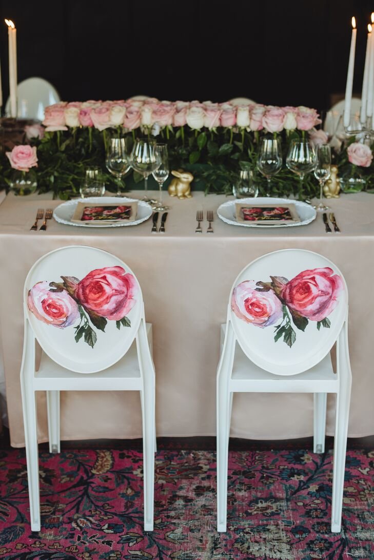 The modern round-backed chairs from the ceremony were repurposed for the reception, where their vibrant pink rose decals worked to transform the rooftop event space into a whimsical garden-like scene. Paired with details such as a lush green garland and bountiful blush blooms, the chairs brought the couple's romantic vision to life.