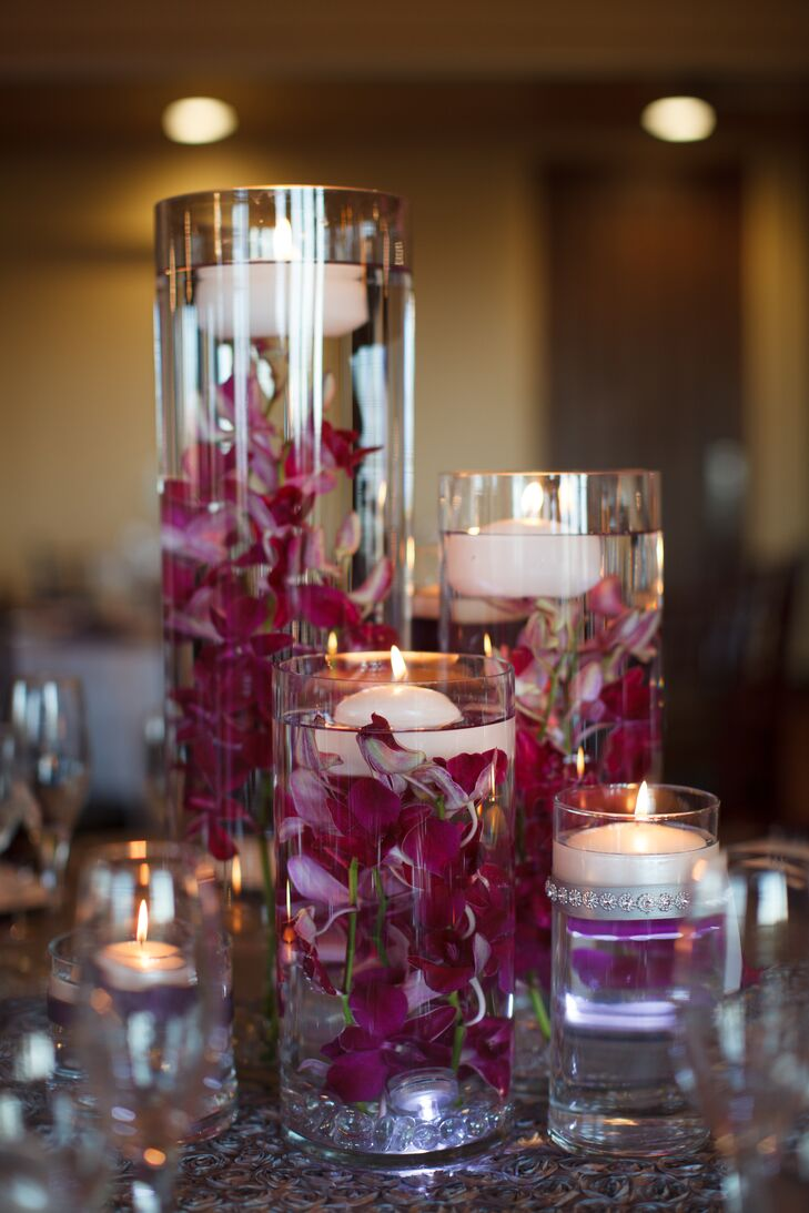 Centerpieces at the reception consisted of cylinder vases of various heights. These vases were filled with purple hydrangeas and floating candles.