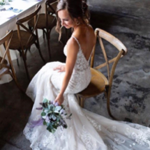 bride in Morilee wedding dress sitting and holding bouquet