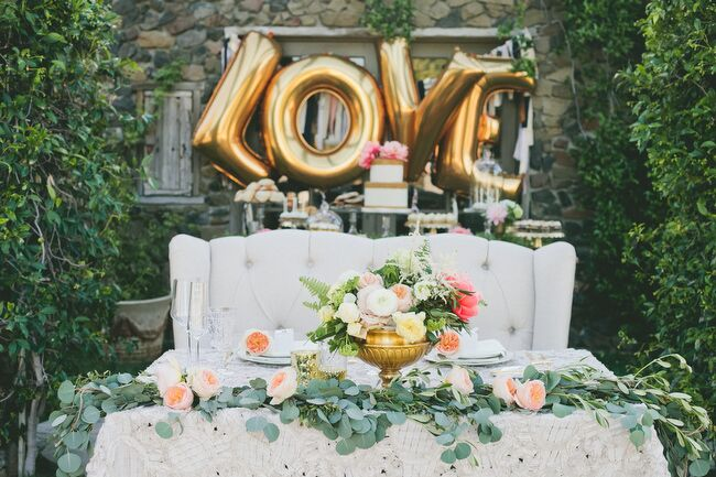 To ensure a few private moments together throughout the evening, Sarah and Brendon opted for a sweetheart table at the reception. It featured the same textured, lacy table linens as the reception's main tables and was decorated with romantic blooms displayed in a gold-footed vase and a garland of silvery eucalyptus dotted with pink garden roses.