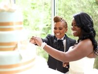 Couple cutting their wedding cake in front of guests during wedding reception.