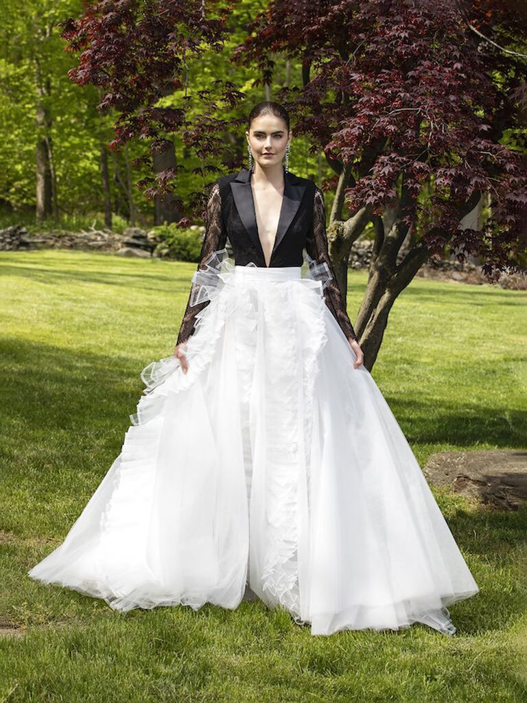christian siriano a line wedding dress with black tuxedo deep-v top with v-neckline lace and long sleeves and white tulle flowy skirt with ruffles and lace