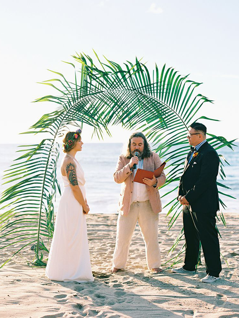 outdoor beach wedding ceremony with palm leaf arch in mexico