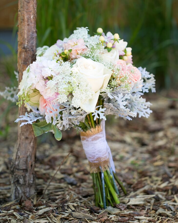 Victoria's Garden florist used dusty miller, mums, baby's breath and roses to create this lace-wrapped bouquet for the bride.