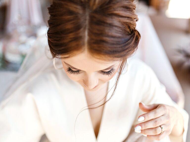 bride in robe looking down