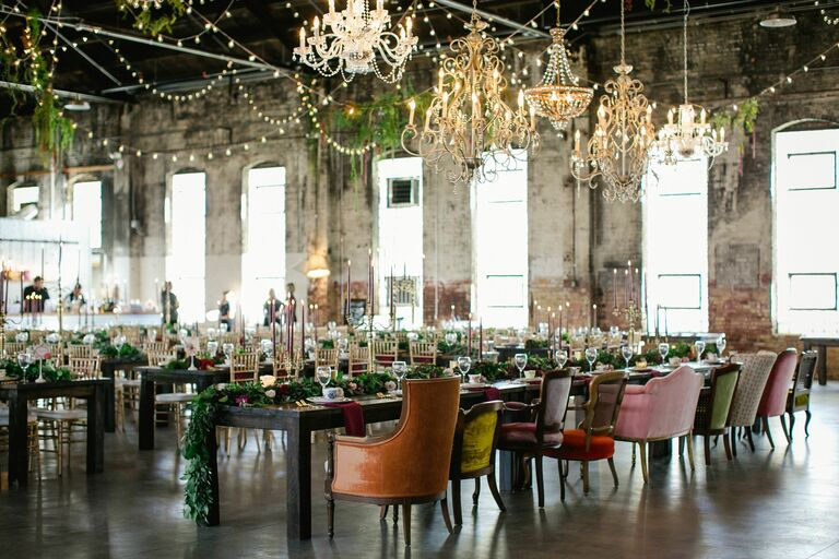 Industrial reception space filled with ornate chandeliers and mismatched chairs