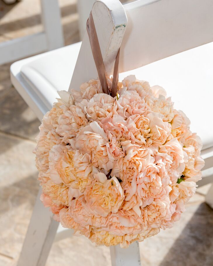 The aisle chairs were decorated with hanging pink rose pomanders.