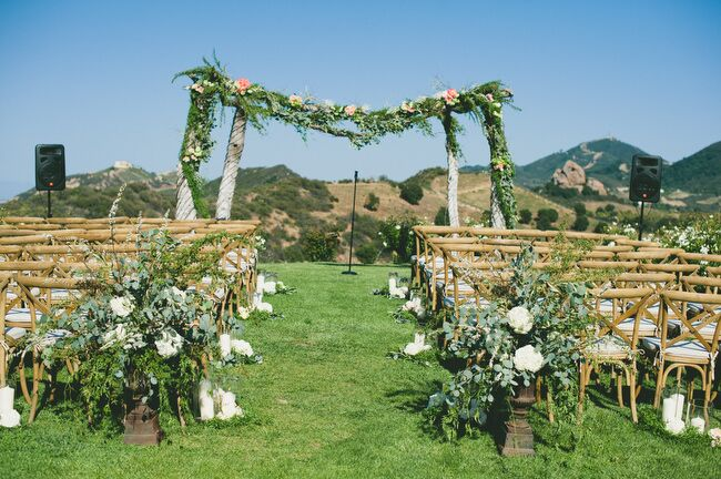 The ceremony was held at Saddlerock Ranch's Chateau Le Dome site, overlooking the rolling hills of Malibu, California, and the Santa Monica Mountains in the distance. To match the Tuscan-like setting, the couple lined the aisles with rustic country chairs, hurricane vases filled with white pillar candles and arrangements of eucalyptus and white peonies.