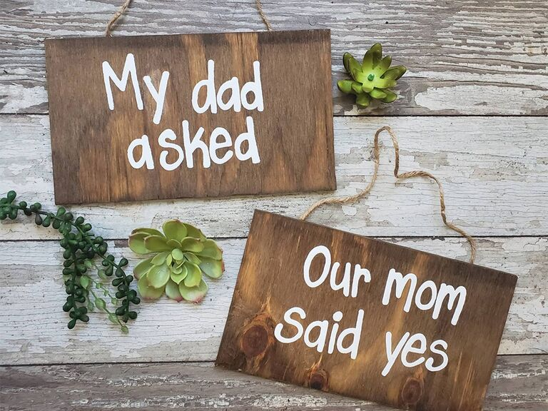 Wooden signs reading 'My dad asked' and 'Our mom said yes' in white type