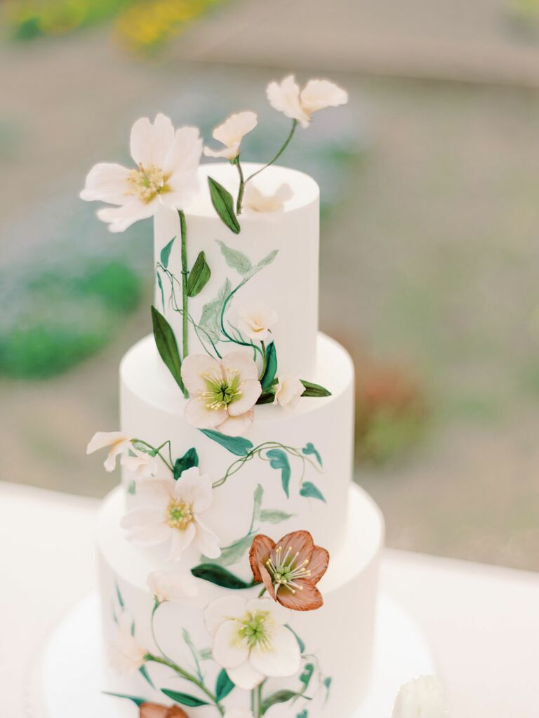 Three-tier white bridal shower cake with hand-painted floral greenery