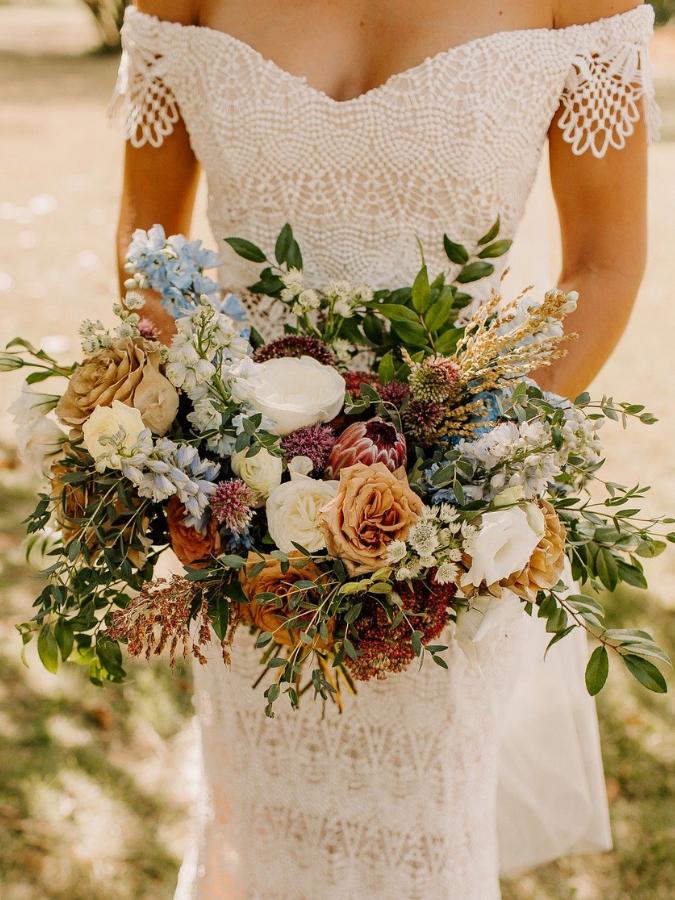 Bride holding boho brown wedding bouquet