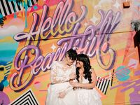 Brides posing in front of '90s-inspired graffiti wall