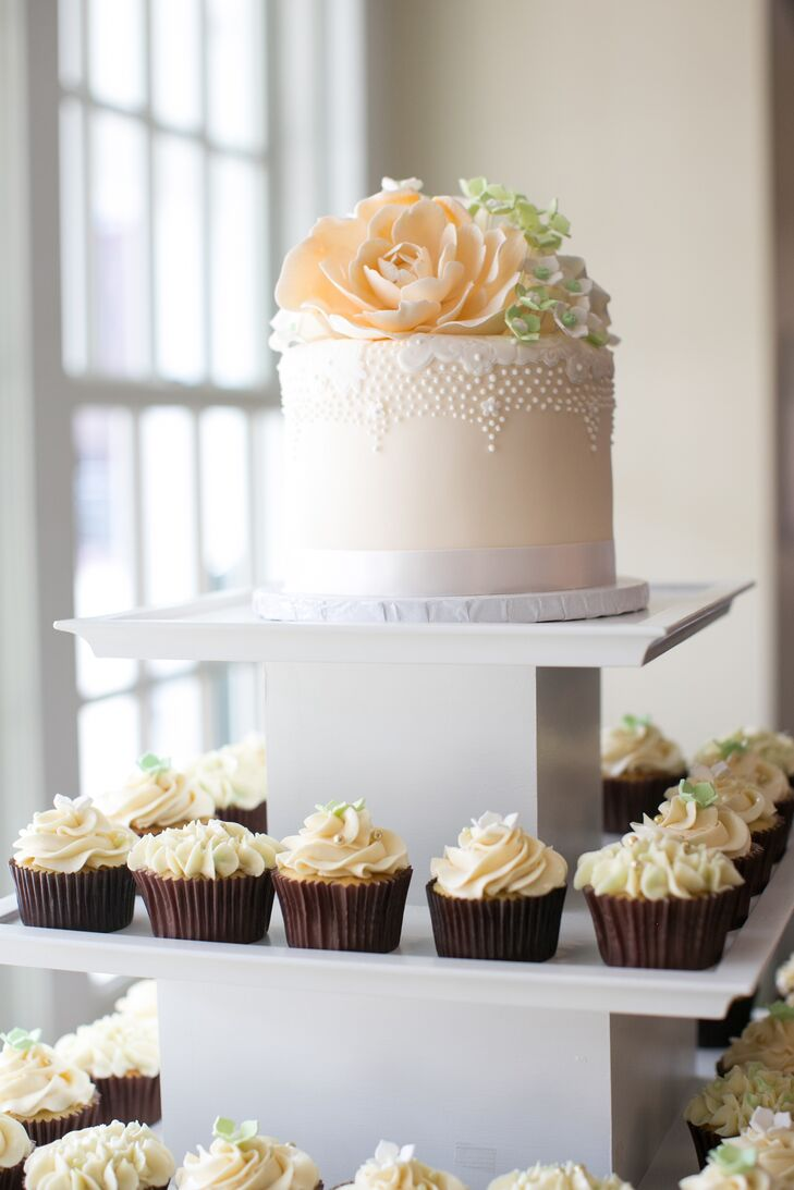 The simple ivory wedding cake was topped with peach and green cake flowers, which stood on top of an assortment of buttercream frosted cupcakes.