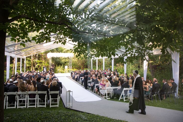"""""""It was a dream of mine to get married where I grew up,"""" Whitney says of exchanging vows in her in Bannockburn, Illinois, backyard under a clear tent draped with greenery."""