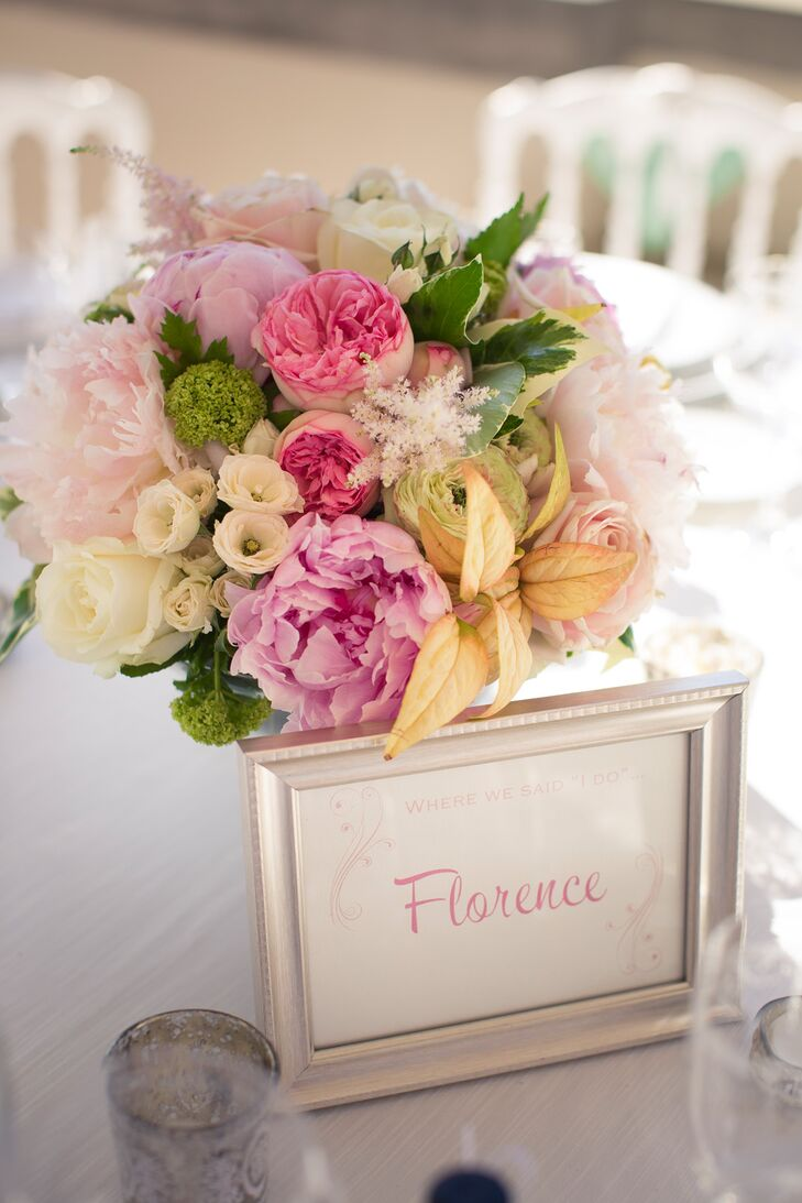 The reception tables were decorated with bouquets of blush and pink peonies, pink garden roses, ivory roses, astilbes and greenery. The tables were named after Zoe and Guy's favorite cities, which were displayed in silver frames.
