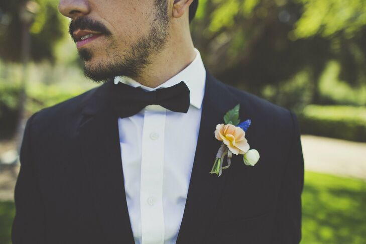 Clay wore a classic tuxedo to complement the elegant style of the wedding. A peach and lavender boutonniere added a hint of color to his ensemble.