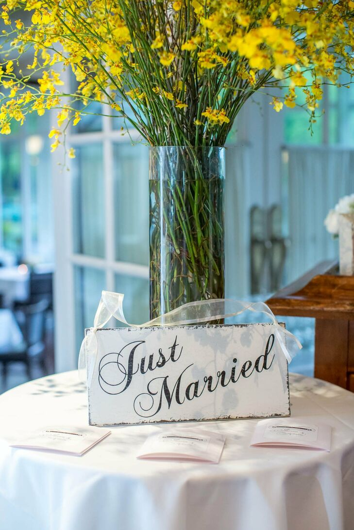 """Matching worn white signs saying """"Just Married,"""" """"Thank You,"""" and other sweet messages decorated the ceremony and reception."""