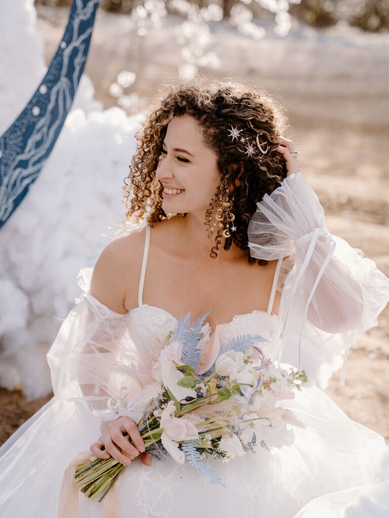 Bride wearing celestial-themed wedding dress with star and moon hair pins and earrings