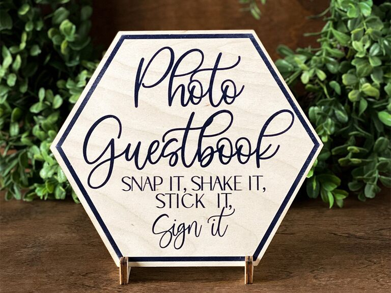 'Photo guestbook' in loopy blue script on white birch hexagon sign