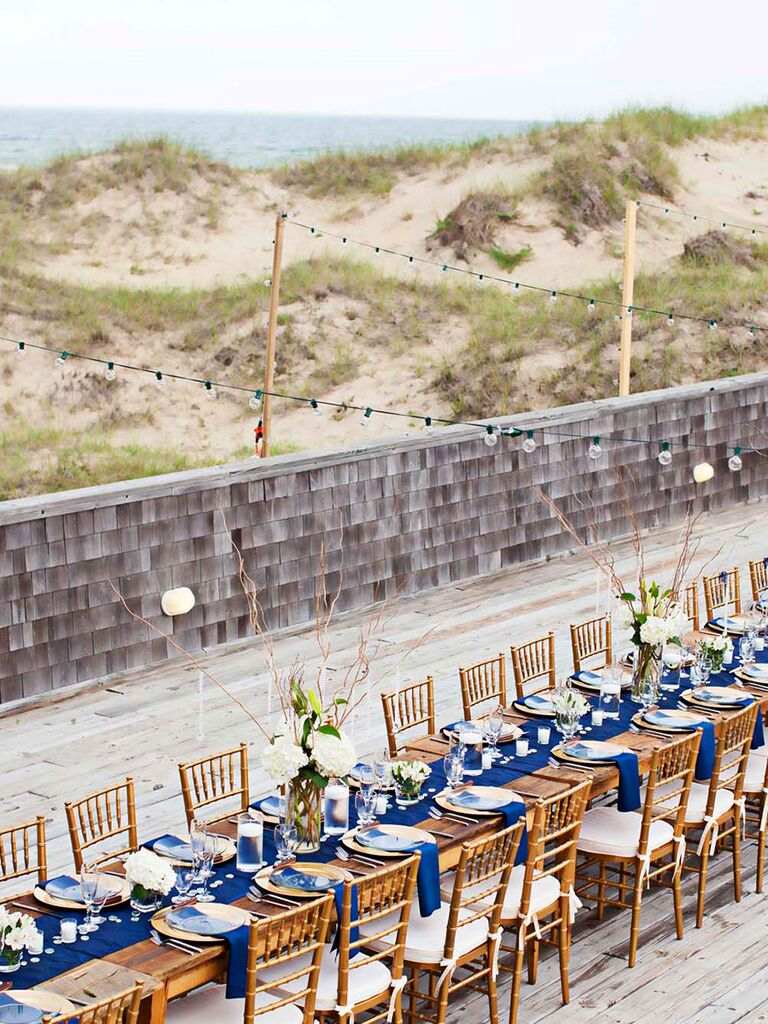 Long reception tables on beach with blue decor string lights